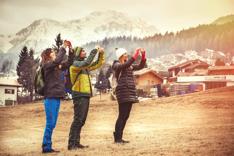 Three friends in the mountains. Taking a picture. Hiking. royalty free stock photo