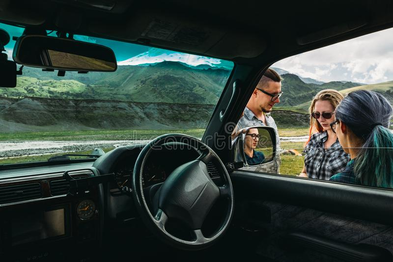 Three friends near the car discuss the route in the journey. A young men and two girls near the car discuss the traffic route during a holiday in the mountains royalty free stock photos