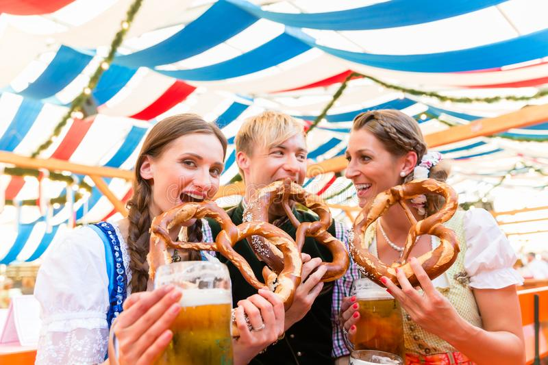 Friends eating giant pretzels and drinking in beer tent. Three friends at the Regensburger Dult eat giant pretzels and drink beer in tent royalty free stock image