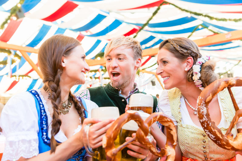 Friends eating giant pretzels and drinking in beer tent. Three friends at the Regensburger Dult eat giant pretzels and drink beer in tent stock image