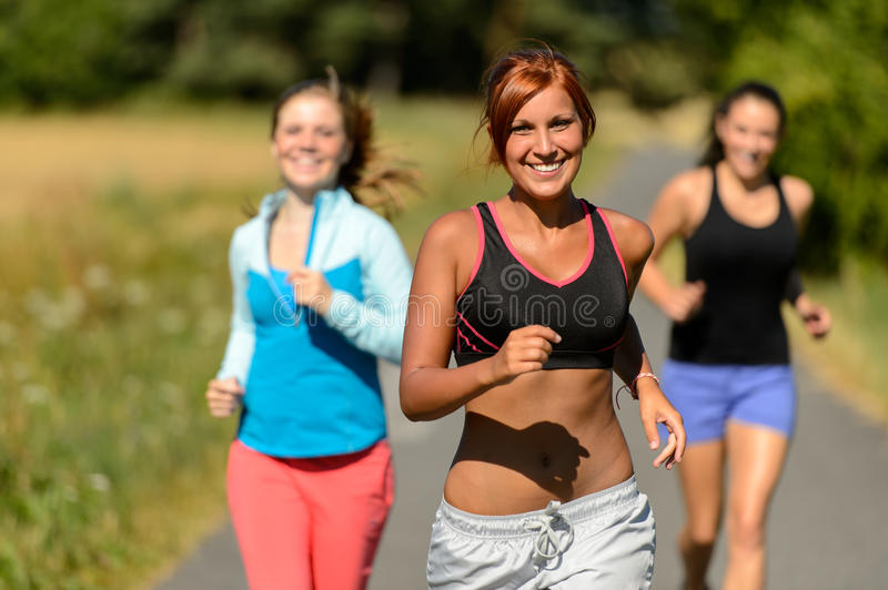 Three friends running outdoors smiling royalty free stock photo