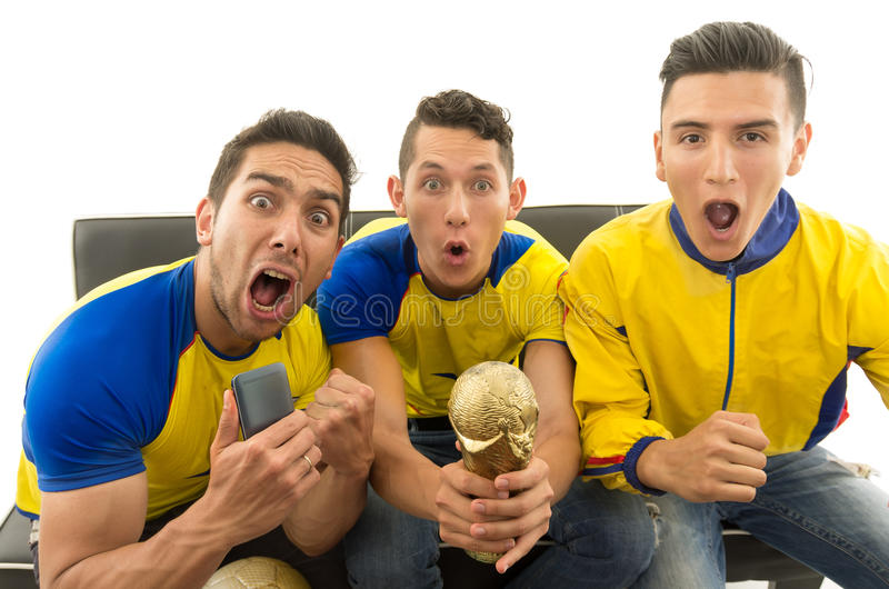 Three friends sitting on sofa wearing yellow sports shirts screaming cheering at camera with enthusiasm, white. Background, shot from above stock photography