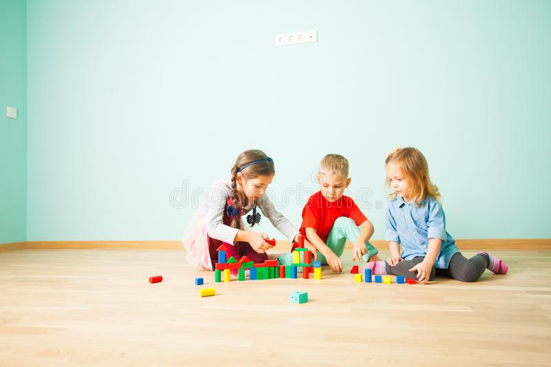 Three friends building with blocks on a floor royalty free stock photos