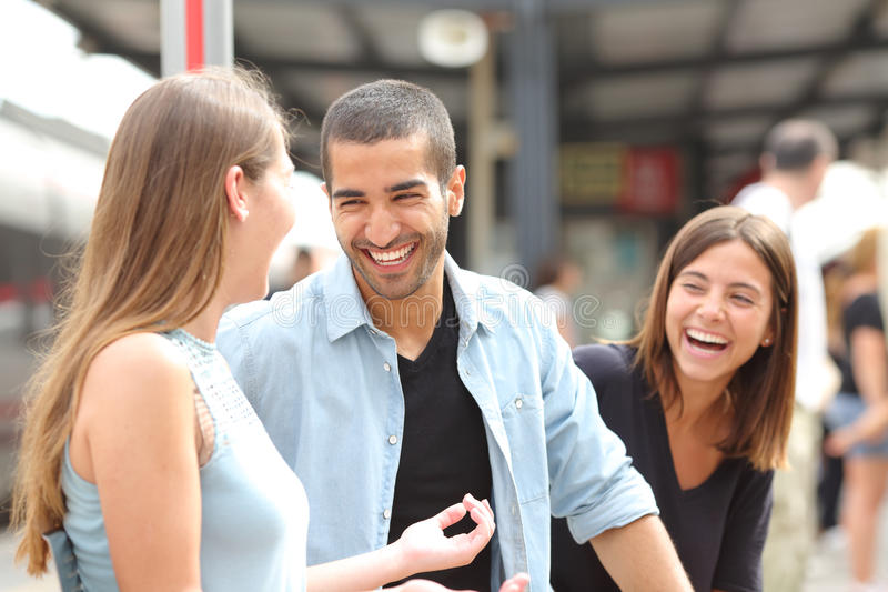 Three friends talking and laughing in a train station royalty free stock photo