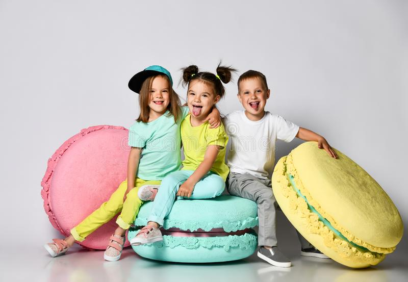Three friends of triplets - two girls and a boy in bright clothes have fun at the birthday party fun room decoration  macarons. Three friends of triplets - two stock images