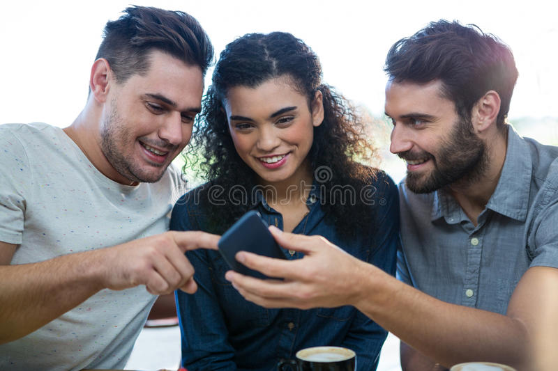 Three friends using mobile phone in the coffee shop stock photo