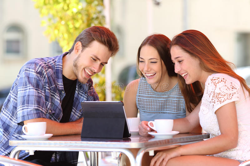 Three friends watching tv or social media in a tablet. Three happy friends watching tv or social media in a tablet in a coffee shop terrace