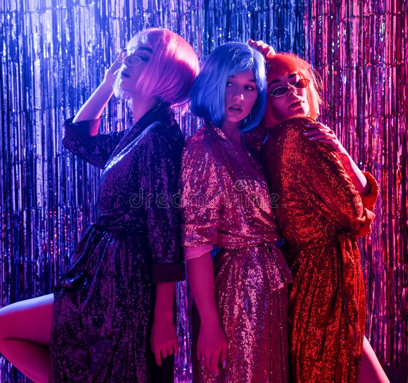 Smiling girls in wigs and stylish glamorous dresses with sequins, in the neon light of a disco. have fun, celebrate something. Three friends in wigs and stylish stock photo