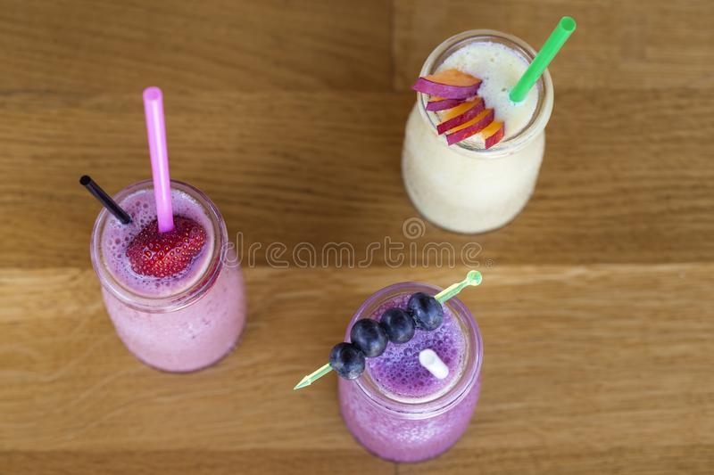 Three fruit milkshakes with fresh organic ingredients including. Strawberries, cranberries and mango blended with yoghurt - top view stock photography