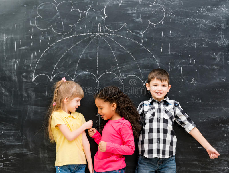 Three funny children with umbrella drawn on the blackboard stock photos