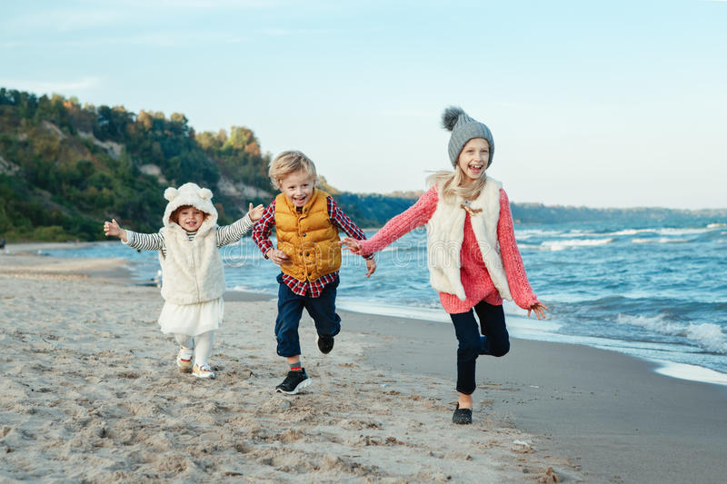 Three funny smiling laughing white Caucasian children kids friends playing running on ocean sea beach on sunset outdoors stock images