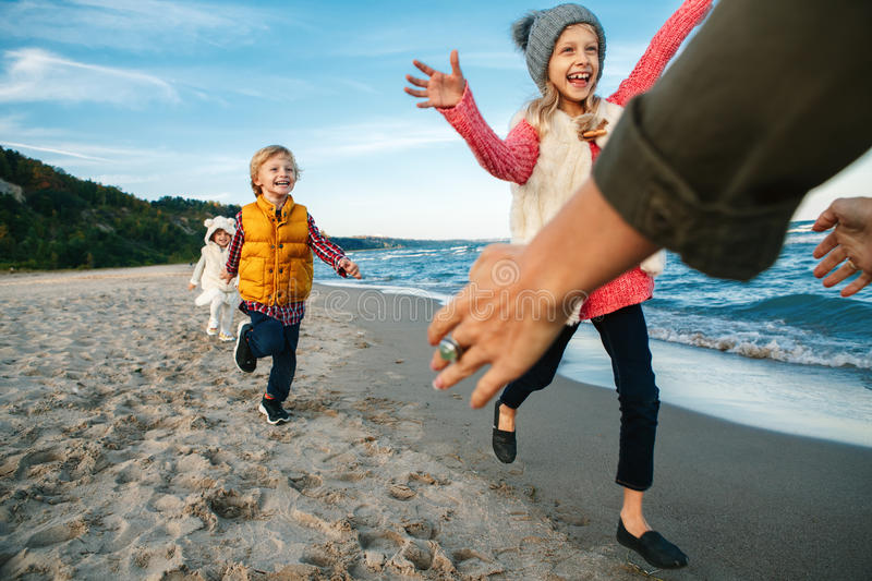 Three funny smiling laughing white Caucasian children kids friends playing running to mother parent adult on ocean sea beach stock images