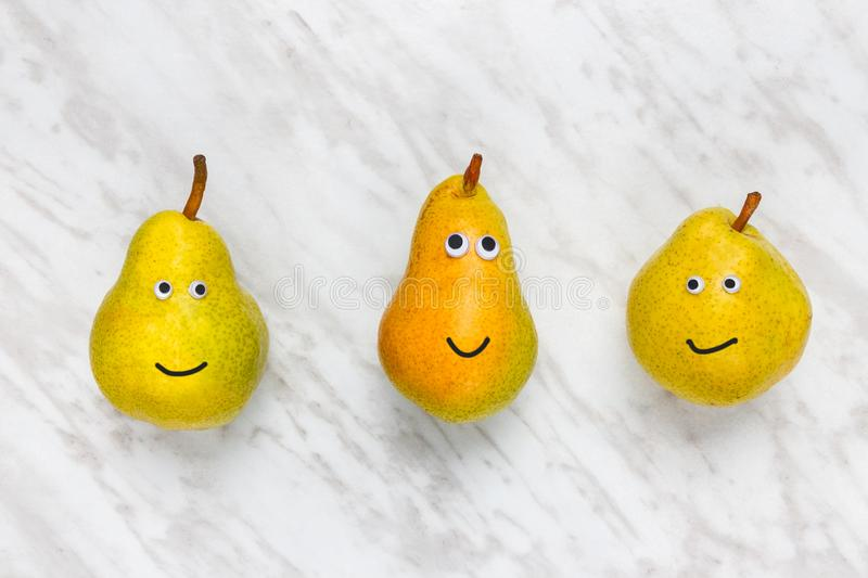 Funny smiling pears on marble background stock images