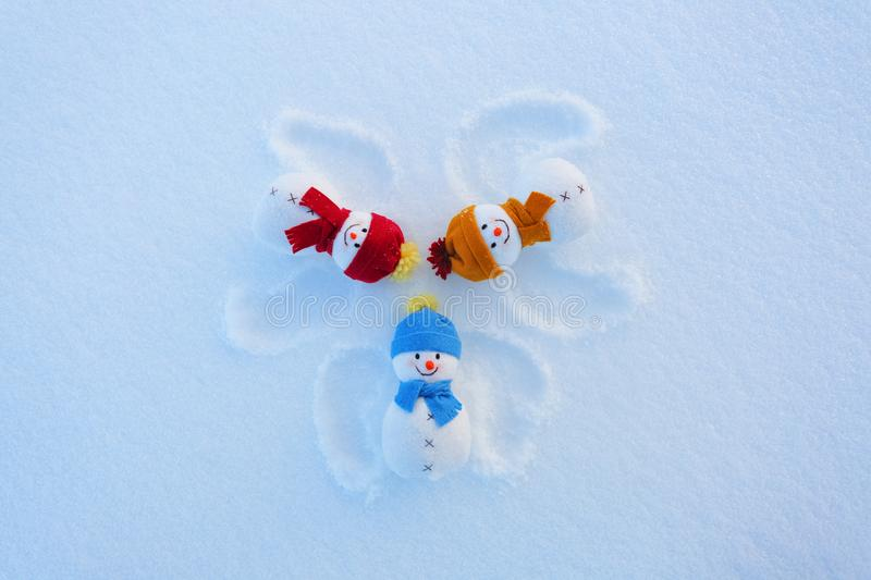 Three funny snowman in hats and scarfs are laying on the snow with drawn wings. Fractured outprints. Happy new year. Nice winter day stock photos