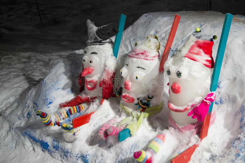 Three funny snowmen with knitted hats sitting stock image