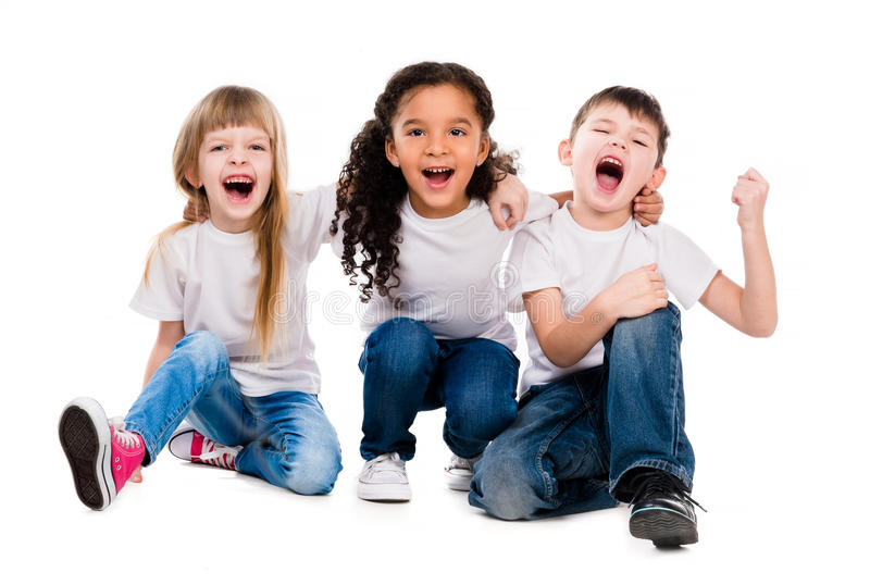 Three funny trendy children laugh sitting on the floor. Isolated on white background royalty free stock image