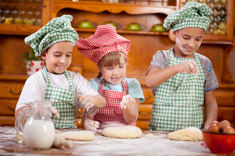 Three funny young child play with a dough in the kitchen. Three smiling child preparing dough for cookies in the kitchen royalty free stock photography
