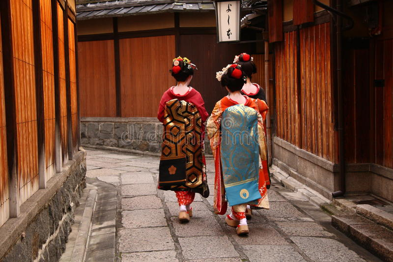 Three geishas. Walking in a narrow street in Kyoto stock images
