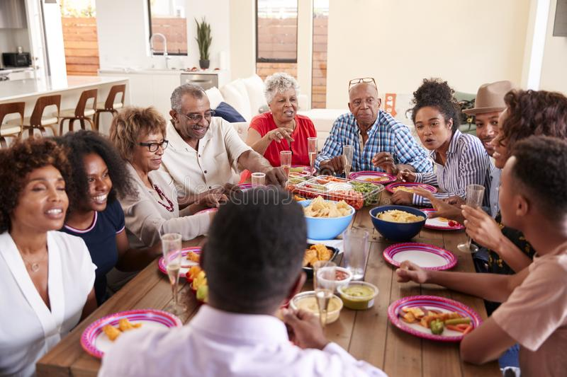 Three generation African American  family sitting at dinner table celebrating together,close up. Three generation black family sitting at dinner table stock image