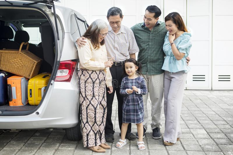Three generation family with car in the garage. Picture of three generation family ready to trip while standing near their car in the house garage stock images