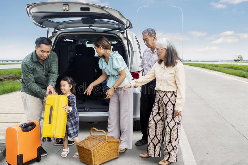 Three generation family with car prepare for holiday. Picture of three generation family preparing suitcase into a car for road trip while standing on the road royalty free stock photos