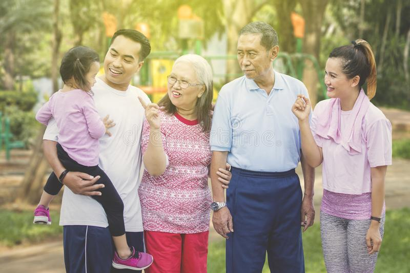 Three generation family chat together at outdoors. Three generation family looks happy while chatting together and standing at outdoors royalty free stock photos