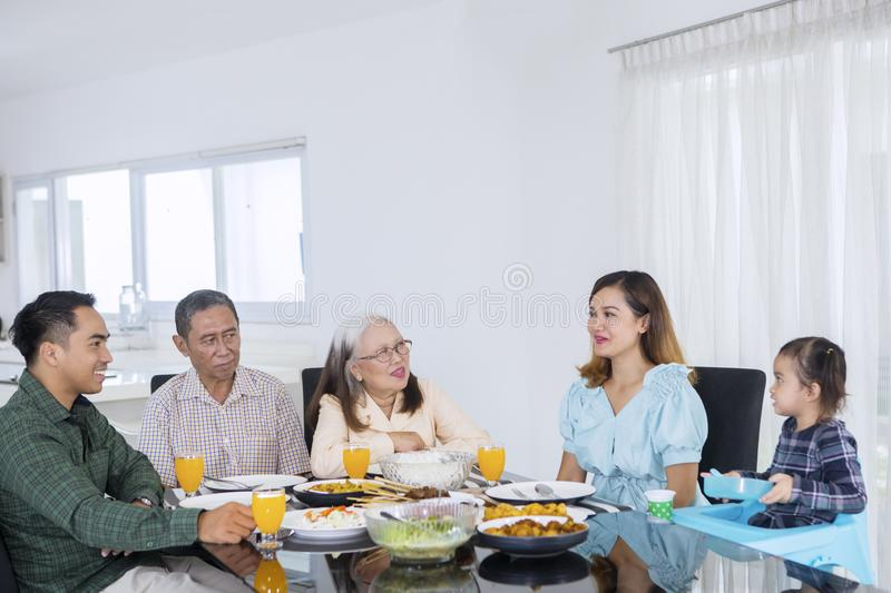 Three generation family chatting at a dining table. Three generation family chatting together while having lunch at a dining table stock image