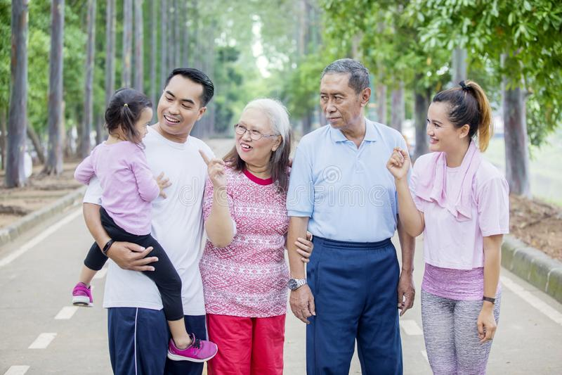 Three generation family chatting in the park. Three generation family looks happy while chatting together and standing in the park stock photo