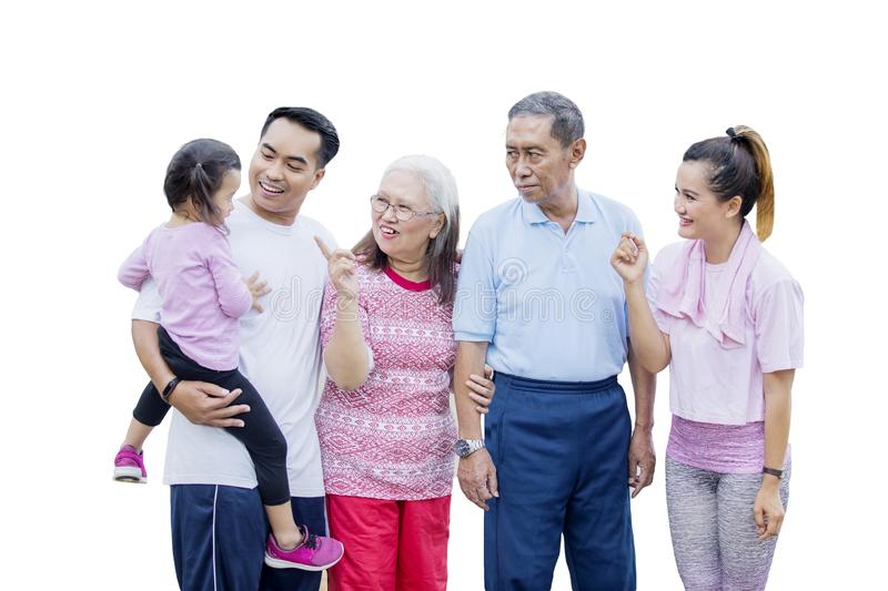 Three generation family chatting in the studio. Three generation family looks happy while chatting together and standing in the studio, isolated on white royalty free stock photo