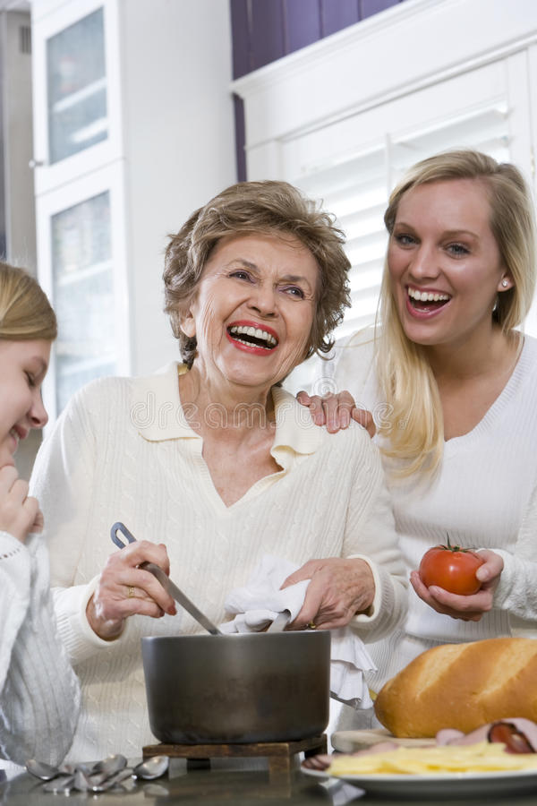 Three generation family in kitchen cooking lunch. Three generation family in kitchen serving lunch, talking and laughing royalty free stock photography