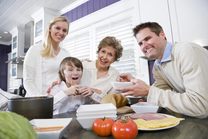 Three generation family in kitchen eating lunch. Talking and laughing stock photo