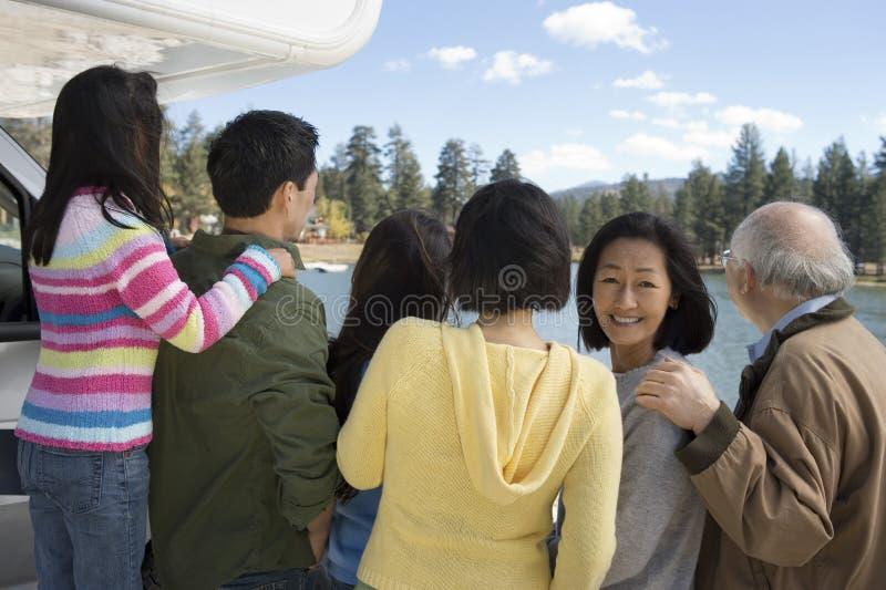 Three-generation family looking at lake stock photography