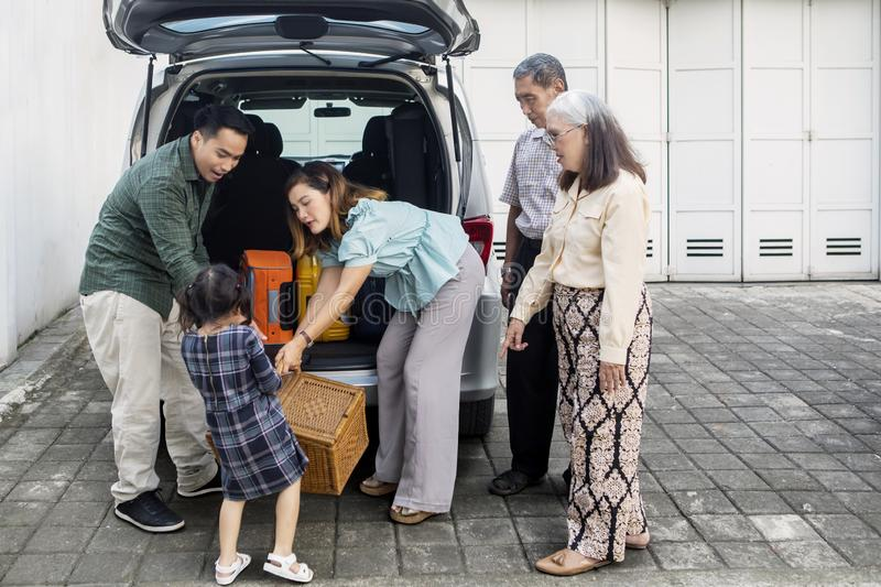 Three generation family ready to trip. While preparing suitcase into a car. Shot in the garage royalty free stock photo