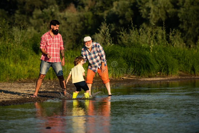 Three generation family. Skipping Stones with Dad adn Granddad. Three different generations ages: grandfather father and royalty free stock photography
