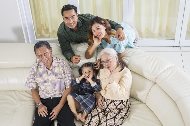 Three generation family smiles at the camera. Top view of three generation family sitting together on the sofa while smiling at the camera stock photography