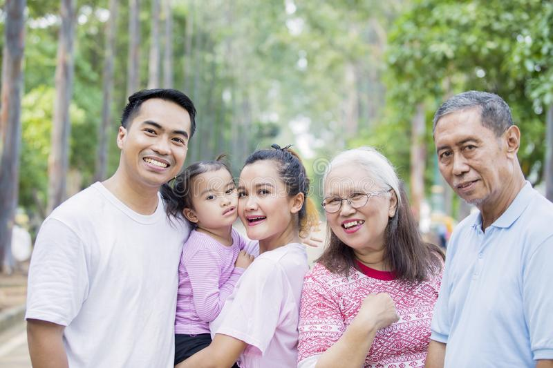 Three generation family smiling at the camera. Picture of Asian three generation family smiling at the camera while standing on the road. Shot at the park stock photo