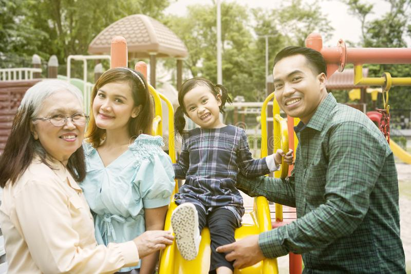 Three generation family smiling in the playground stock images