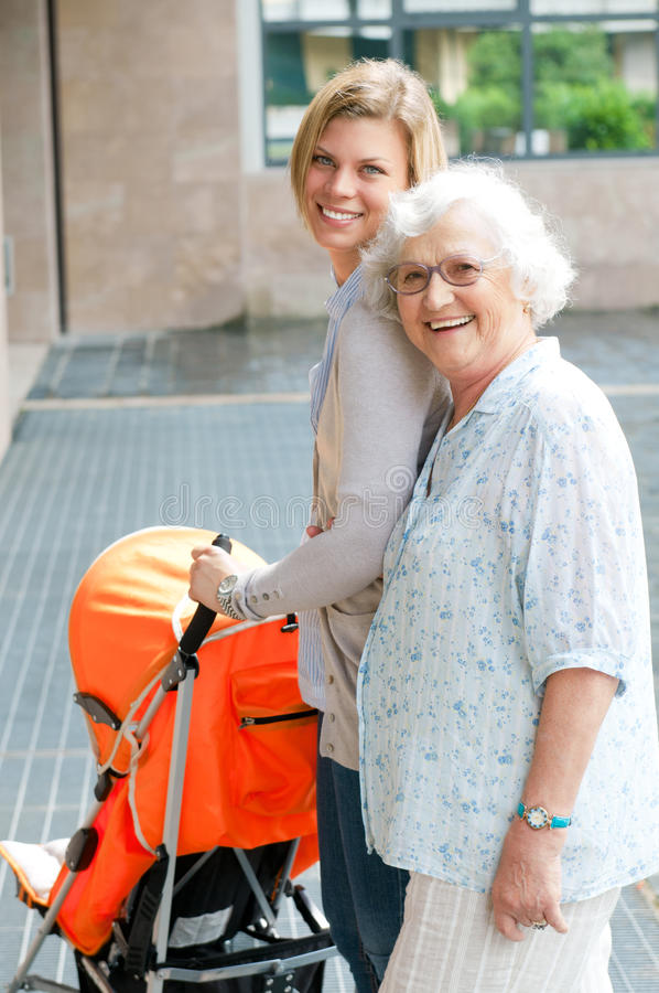 Three generation family taking a walk. Happy smiling grandmother walking with her grandson and pushing a baby stroller, three generation family outdoor stock images