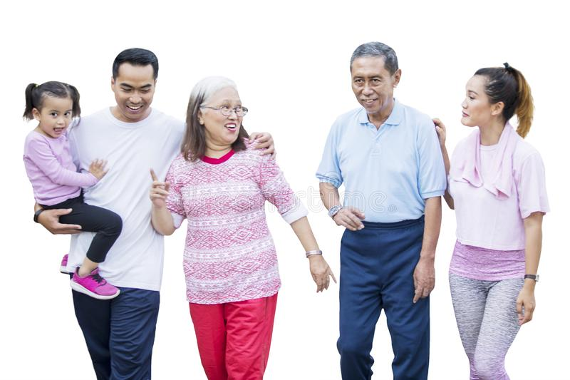 Three generation family walks together in the studio. Three generation family looks happy while walking together in the studio, isolated on white background stock images