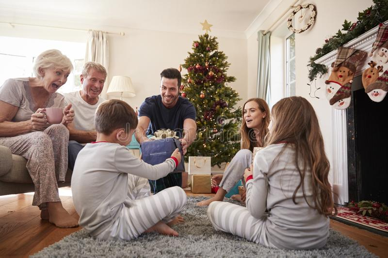 Three Generation Family Wearing Pajamas In Lounge At Home Opening Gifts On Christmas Day stock image