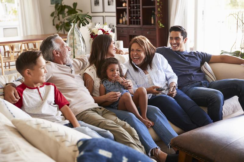 Three generation Hispanic family sitting on the sofa watching TV, grandmother using remote control stock images