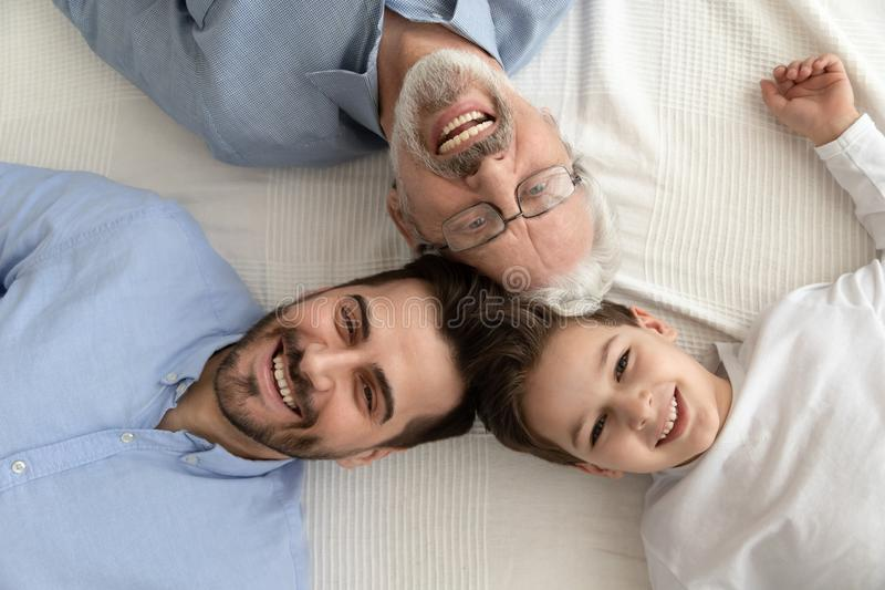Three generation men family lying in circle, portrait, top view. Happy intergenerational 3 three generation men family concept lying in circle close up portrait stock photo