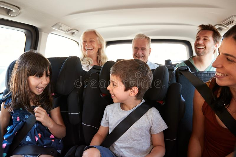 Three generation white family sitting in two rows of passenger seats in a car, looking at each other stock photography