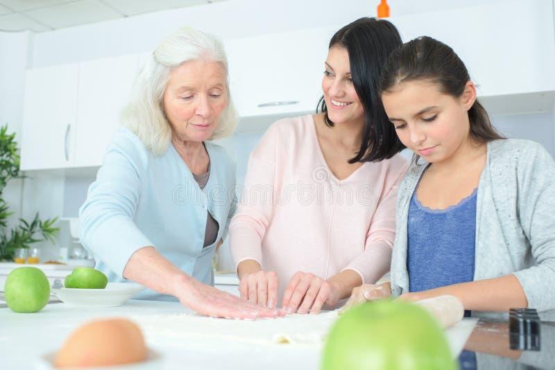 Three generation women making apple pie stock photo