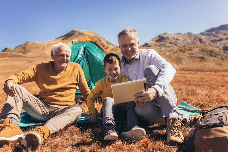 Three generations of family camping together in the autumn royalty free stock photos
