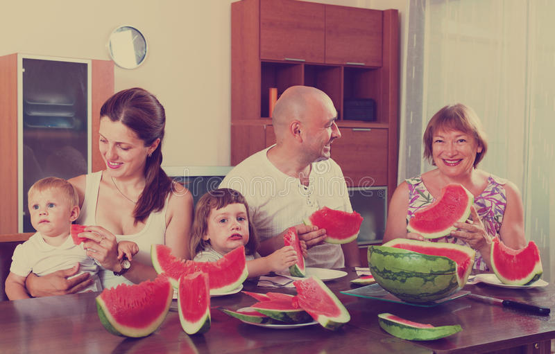 Three generations family eating watermelon. Portrait of happy three generations family eating watermelon at home stock images