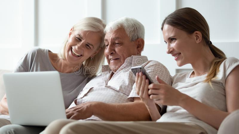 Three generations family with modern gadgets at home. Three generations family with gadgets at home, seated on sofa adult daughter with smartphone and elderly royalty free stock photography