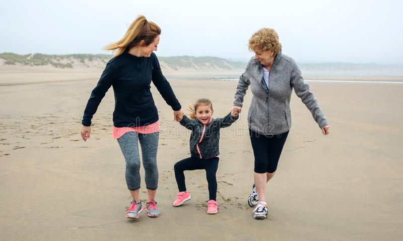 Three generations female running on the beach. In autumn stock photography