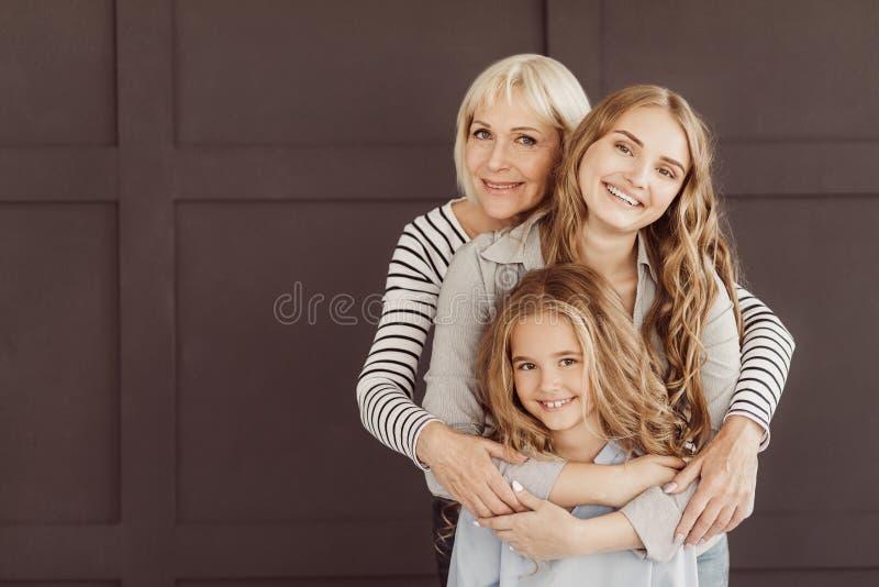 Three generations of happy women looking at camera stock image