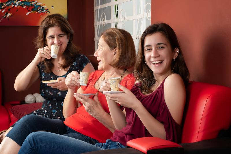 Three generations of hispanic women laughing and drinking coffee stock photo